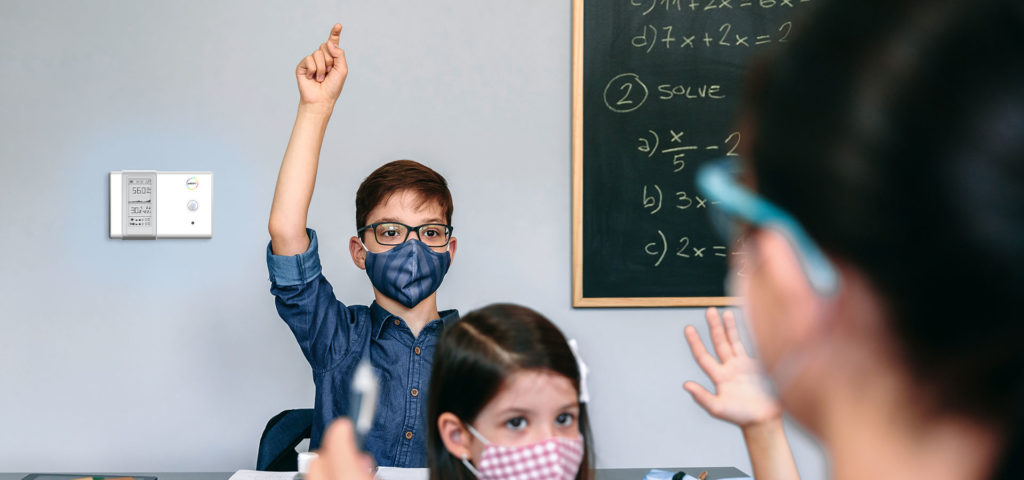 Students with face masks raising their hands at school with their female teacher
